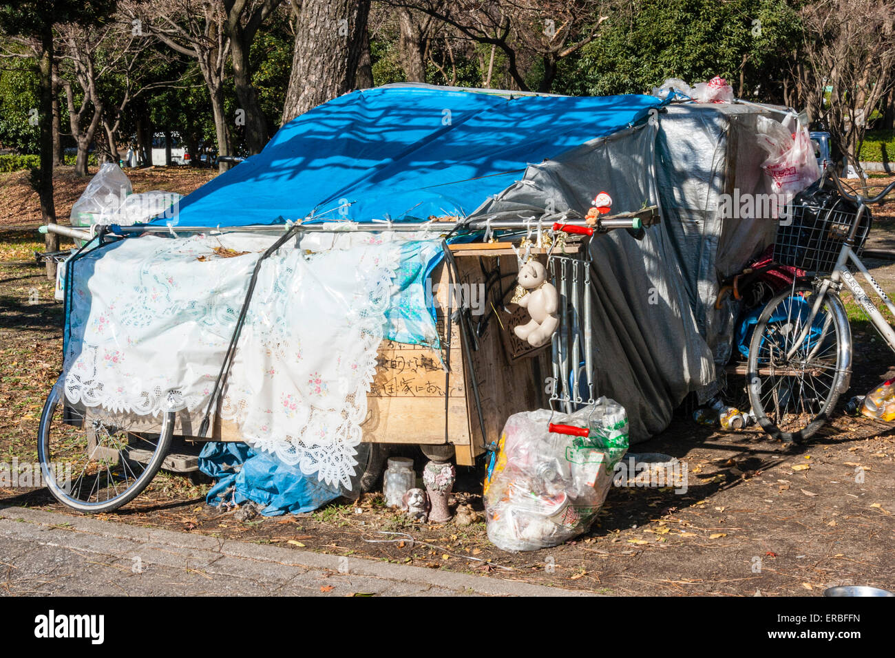 Japan, Nagoya. Typical blue tarpaulin homeless shelter in the park, belongings neatly stored outside, bike and bags - Stock Image