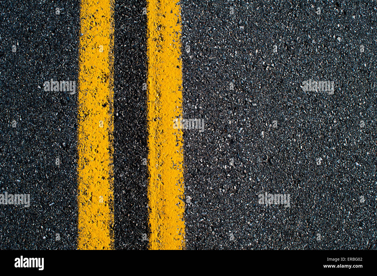 A double-yellow 'no passing' line on an asphalt road. - Stock Image