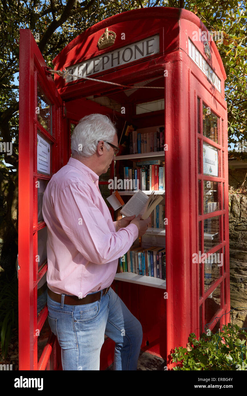A man reads book in the Thurlestone book exchange, located in an old telephone box in the village of Thurlestone, - Stock Image