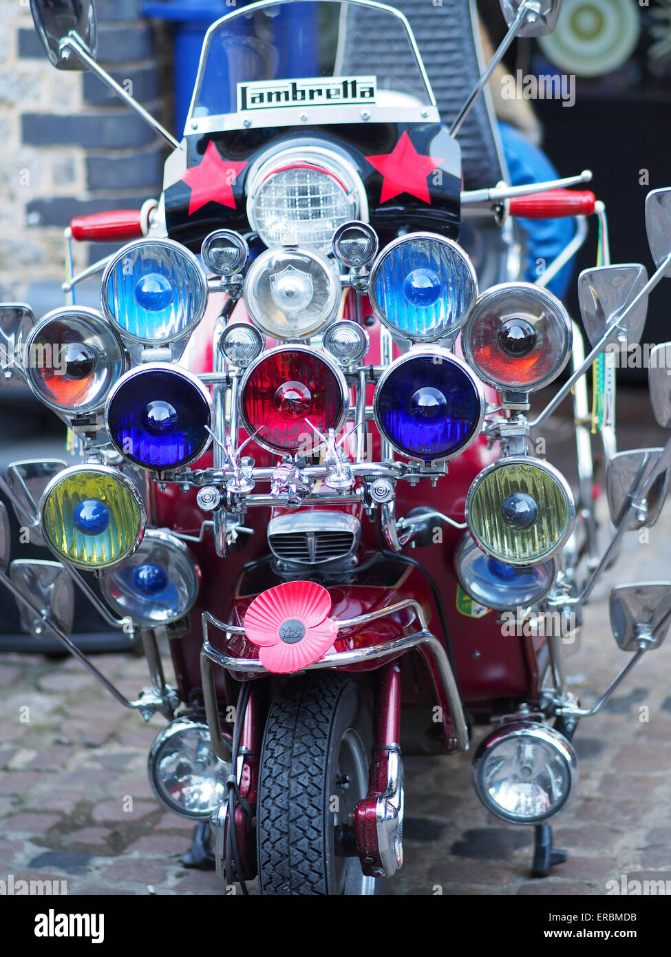 Close-up front view of a Lambretta scooter with lots of colourful headlights - Stock Image