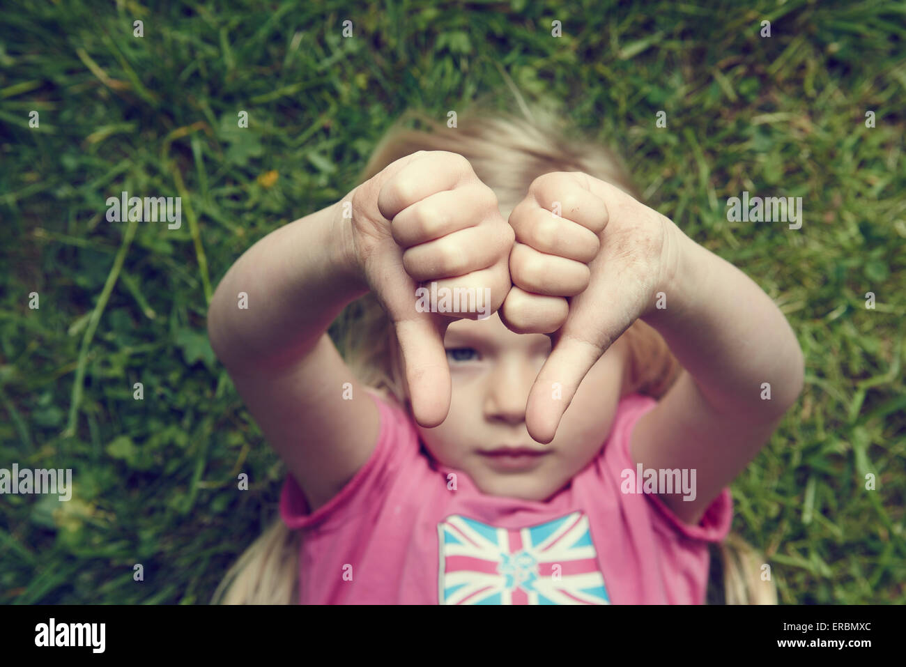 Displeased girl gesturing thumbs down lying on green grass background - Stock Image