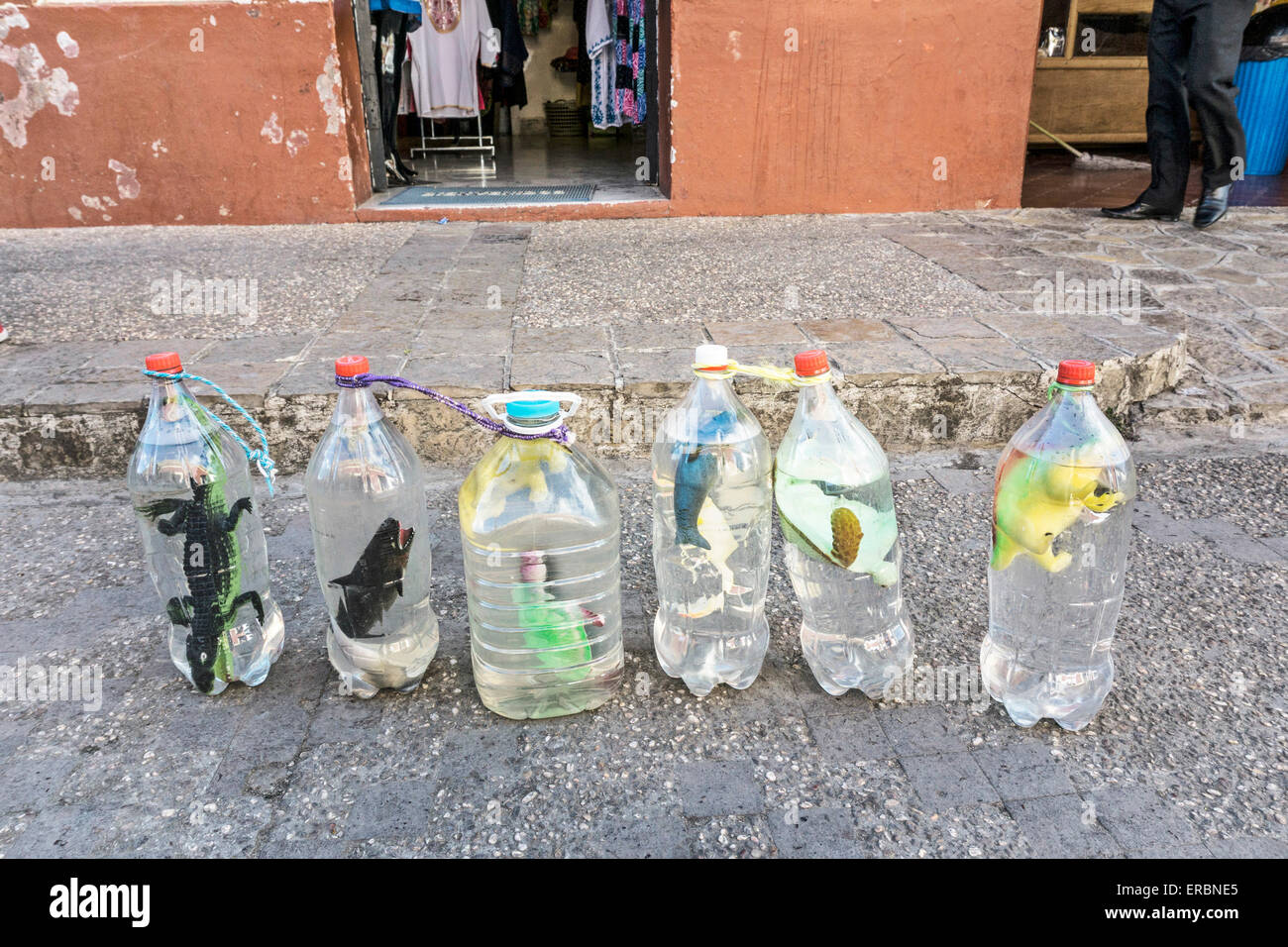 toy miniatures floating in cheap recycled bottles are fun faux aquatic specimens for sale in street San Cristobal - Stock Image