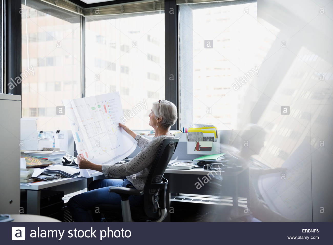 Architect reviewing blueprints at office desk - Stock Image