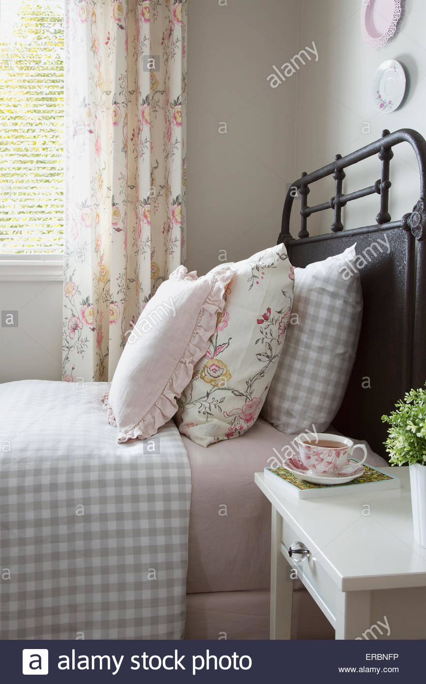 Pastel and gingham pillows on bed - Stock Image