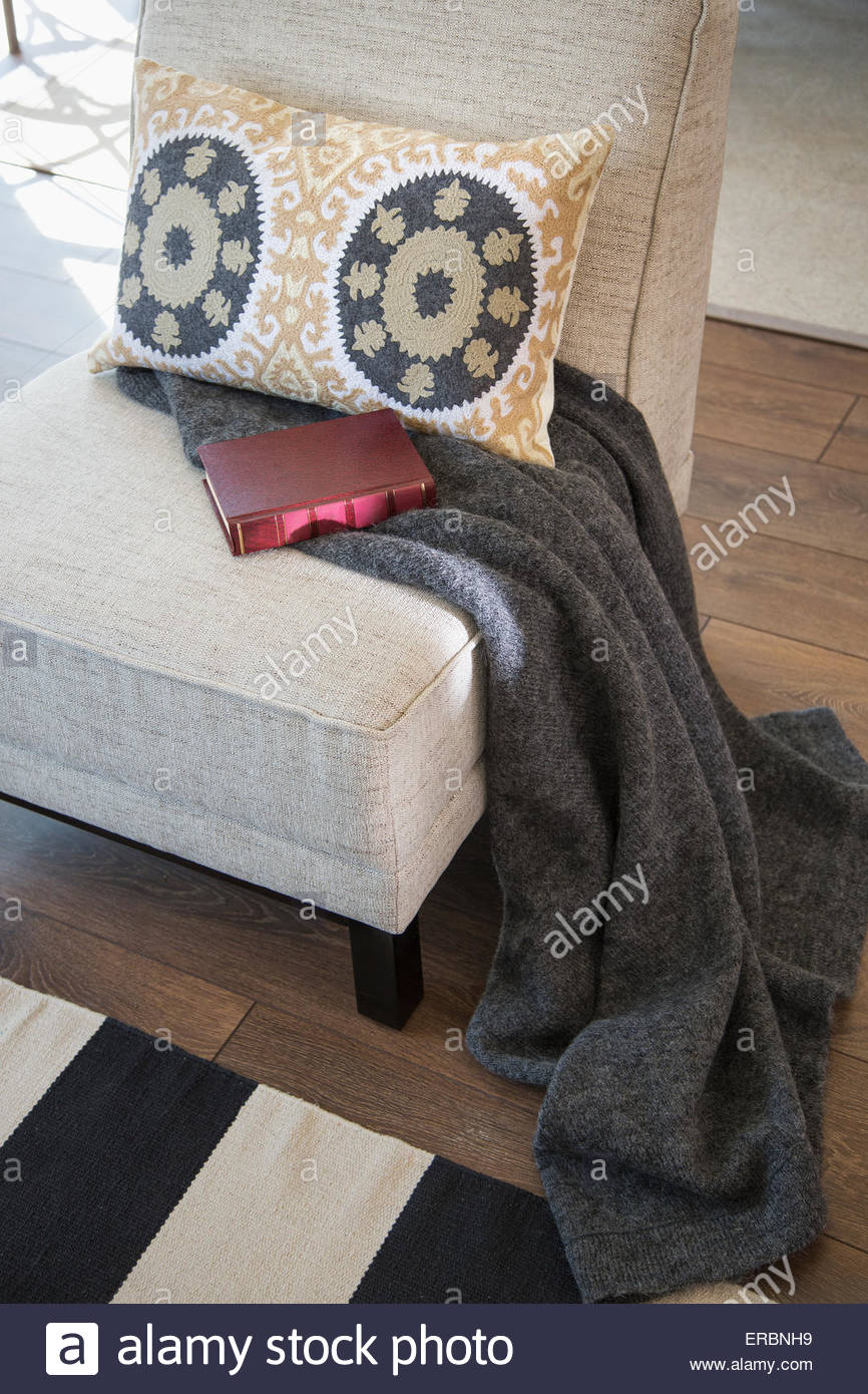 Pillow, blanket and book on chair - Stock Image