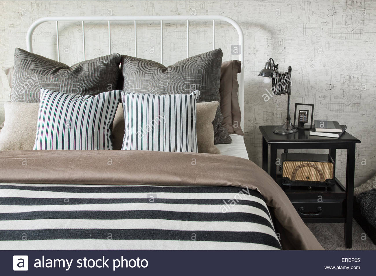 Striped and patterned pillows and blanket on bed - Stock Image