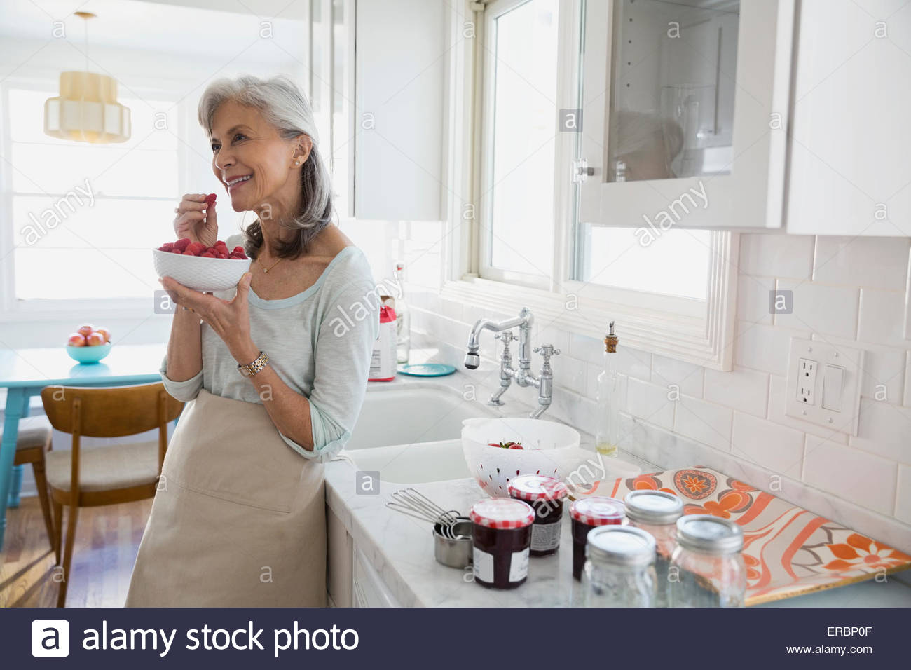 Smiling woman making jam with berries in kitchen - Stock Image