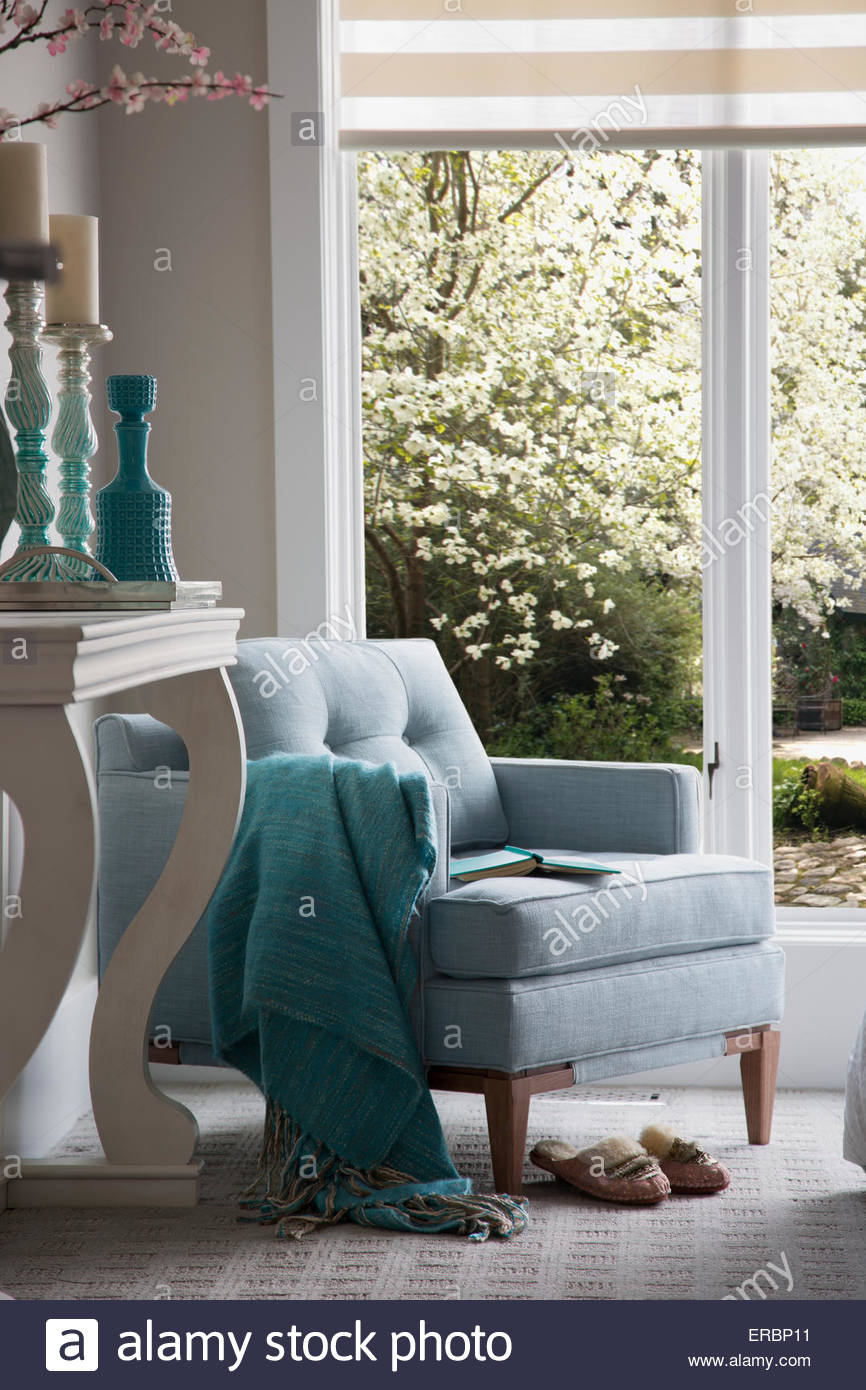 Turquoise decor and armchair by window - Stock Image