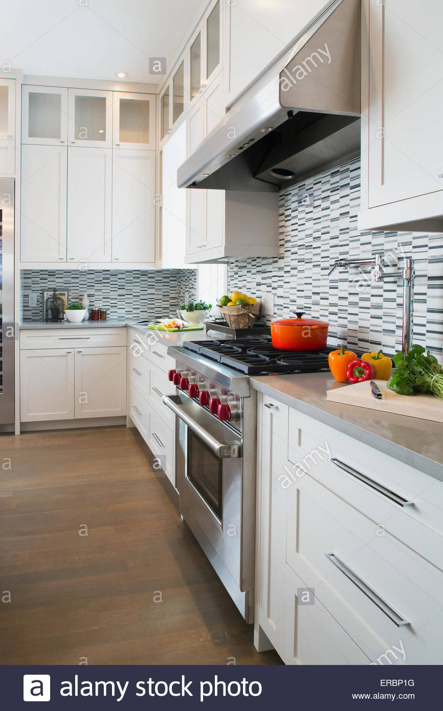 Modern white kitchen with stainless steel range - Stock Image