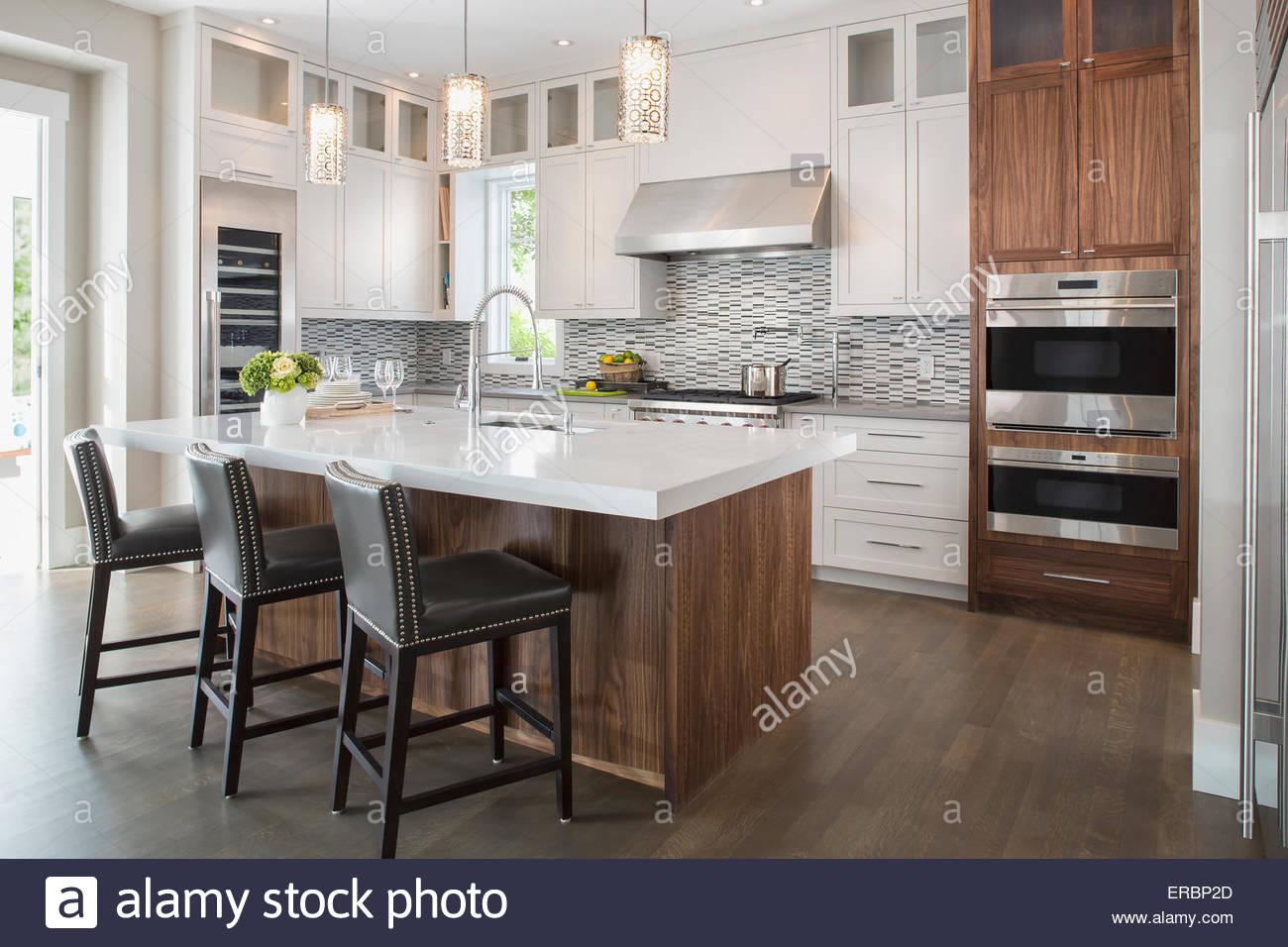 Pendant lights over modern white kitchen island - Stock Image
