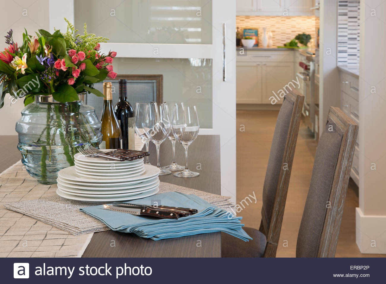 Flower bouquet and stacked place settings dining table - Stock Image