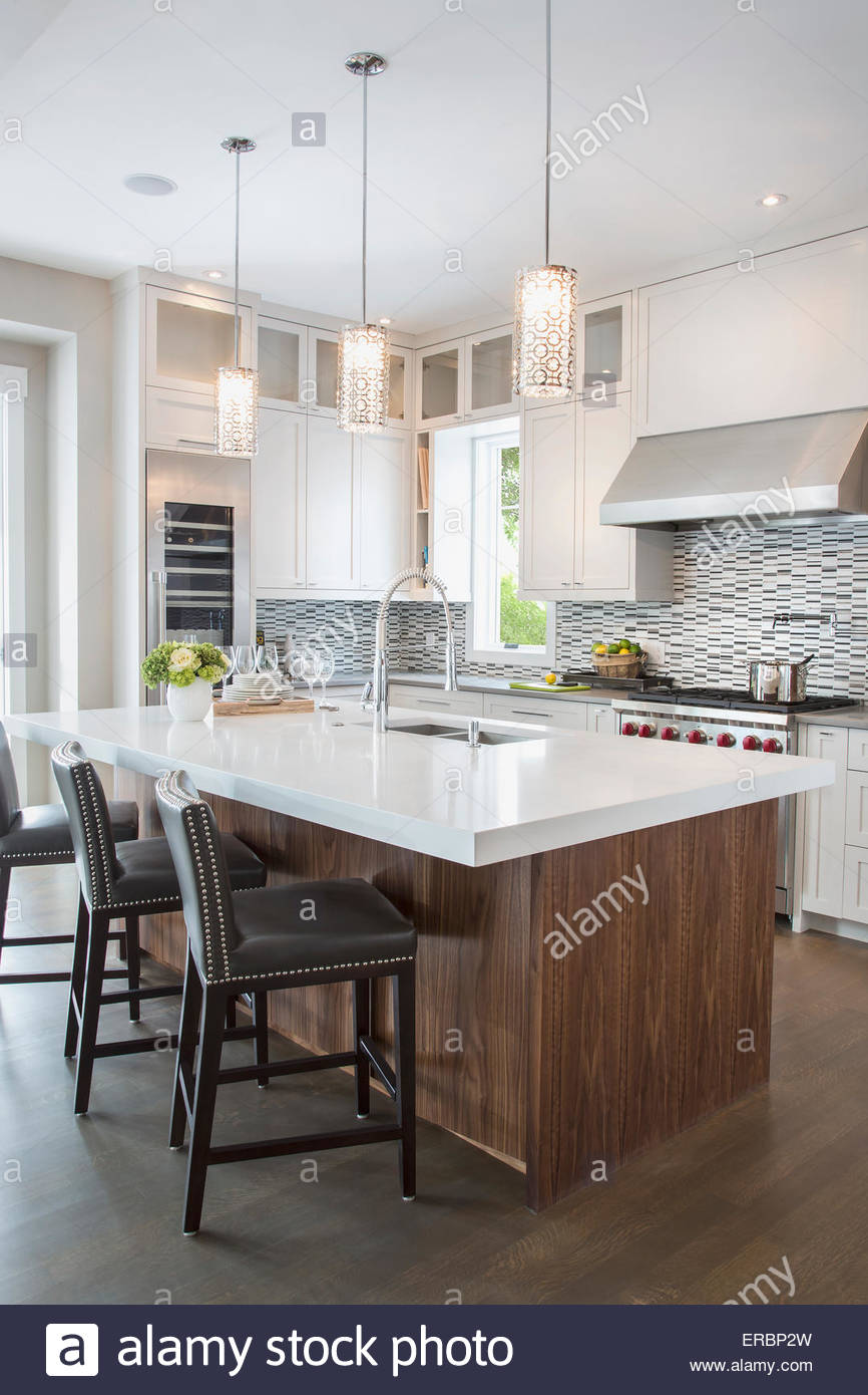 Pendant lights over modern white kitchen island Stock Photo ...