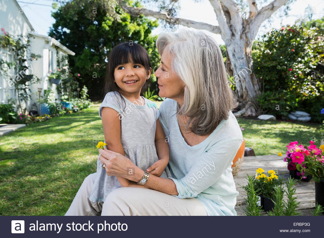 Granddaughter and grandmother hugging in backyard garden - Stock Image