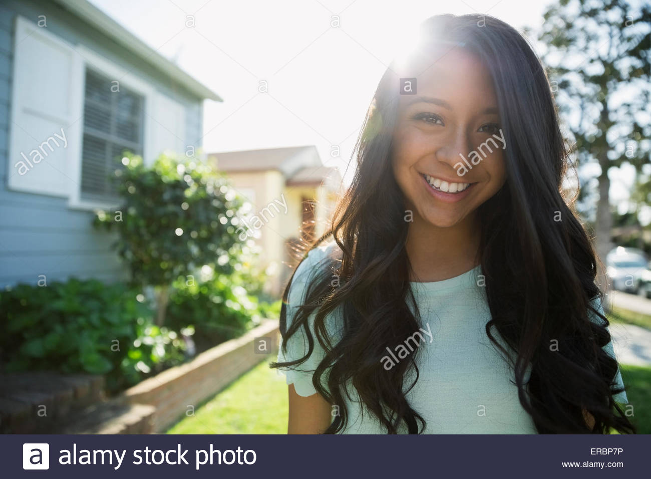 Portrait smiling brunette teenage girl sunny front yard - Stock Image