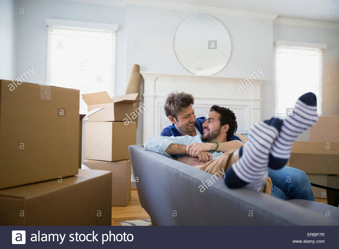 Affectionate homosexual couple relaxing sofa among moving boxes - Stock Image