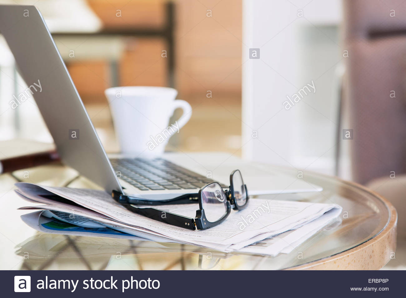 Eyeglasses and newspaper next to laptop and coffee - Stock Image