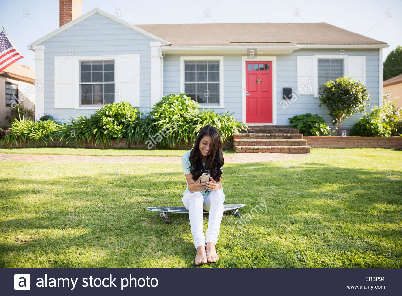 Brunette teenage girl texting on skateboard front yard - Stock Image