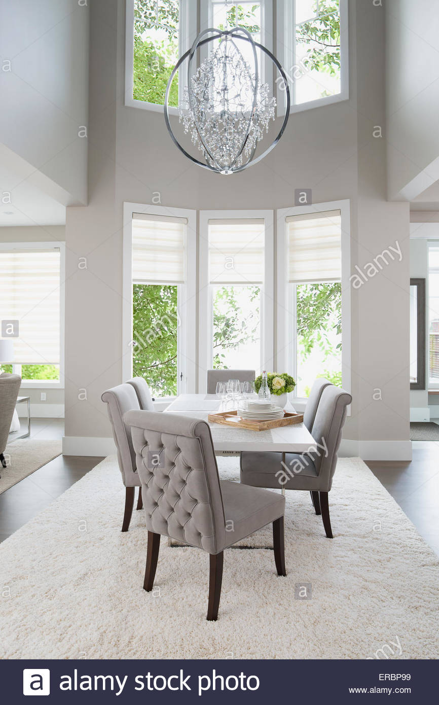 Vaulted ceiling chandelier hanging over elegant dining table - Stock Image