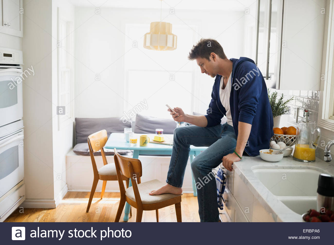 Casual man texting cell phone on kitchen counter - Stock Image