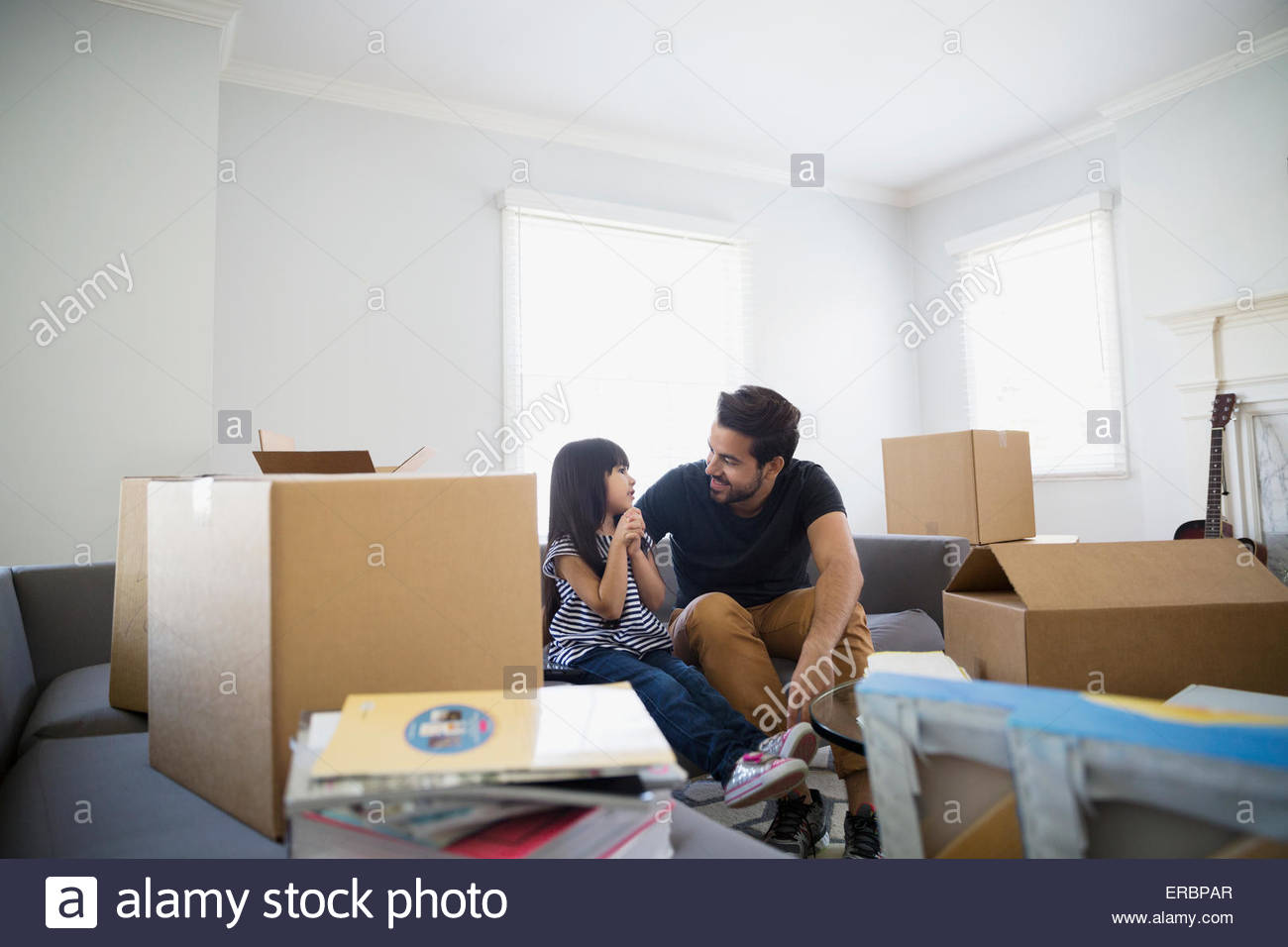 Father and daughter talking among moving boxes - Stock Image