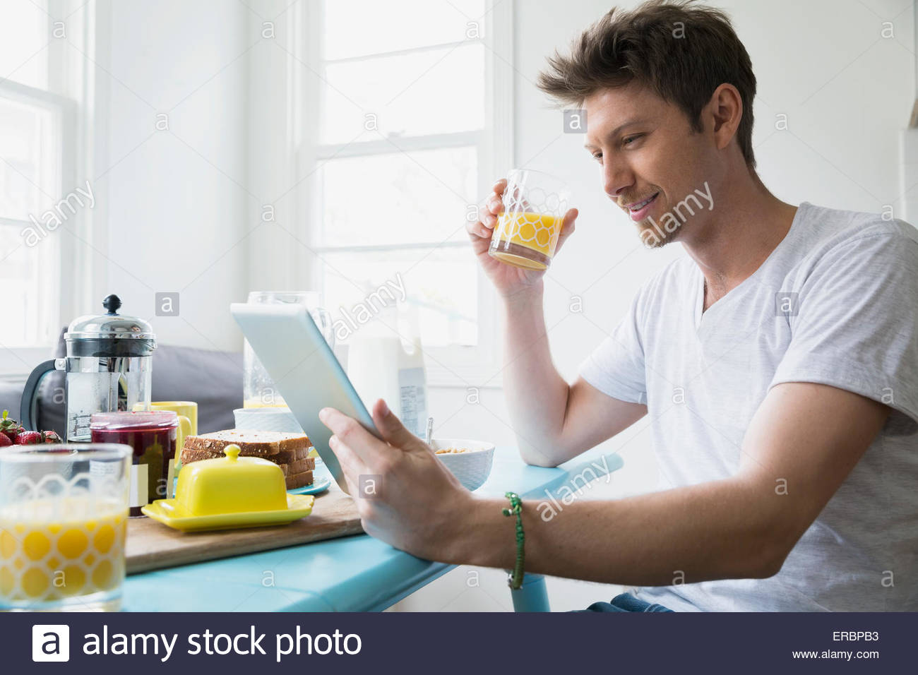Man drinking orange juice and using digital tablet - Stock Image