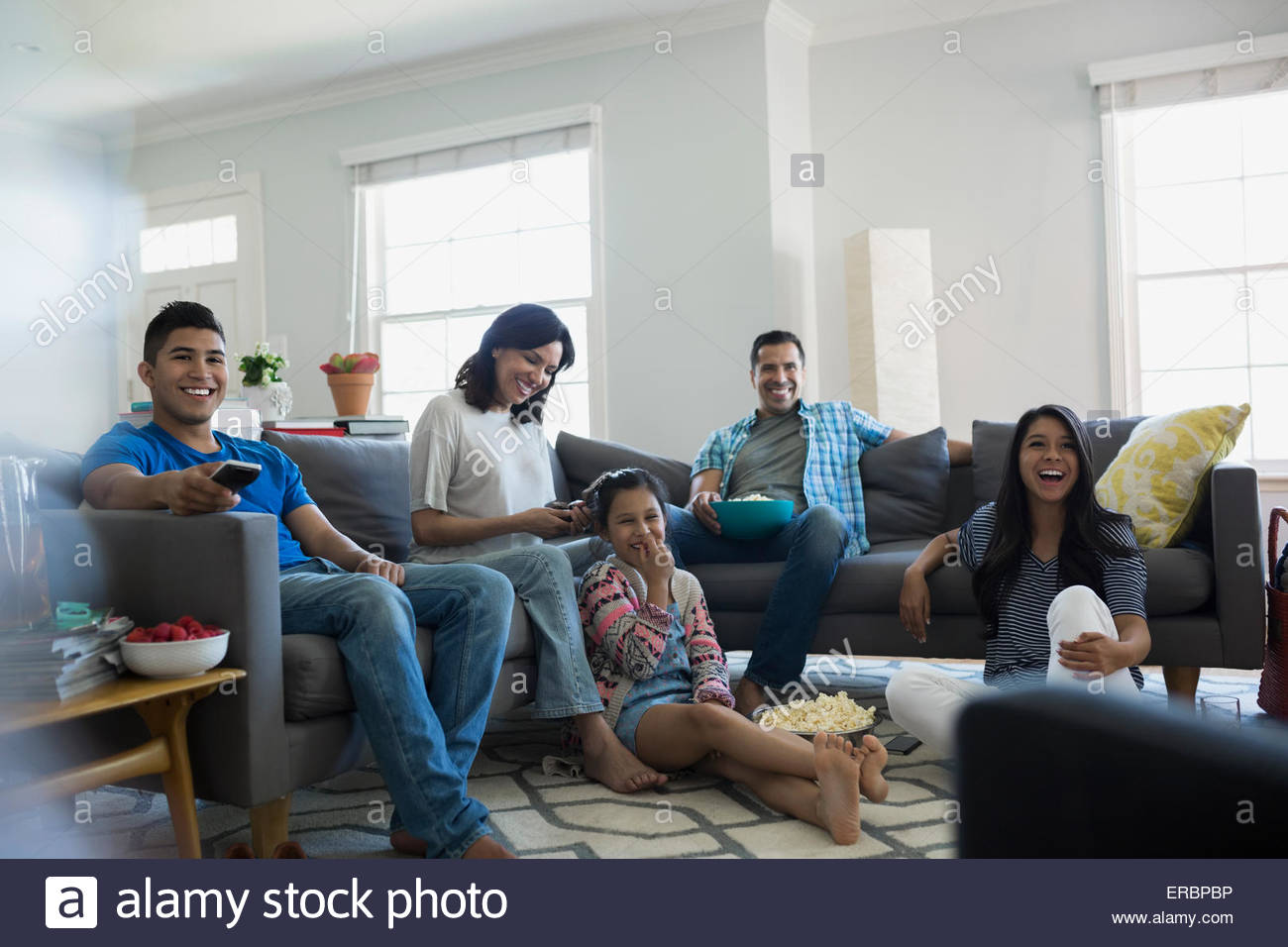 Family watching TV with popcorn in living room - Stock Image