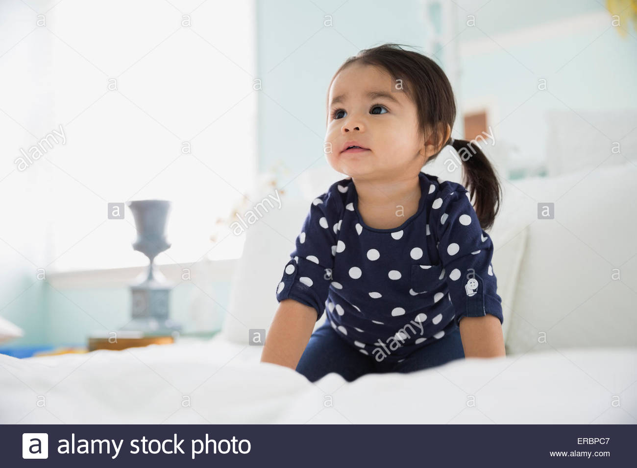 Curious brunette girl looking up on bed - Stock Image
