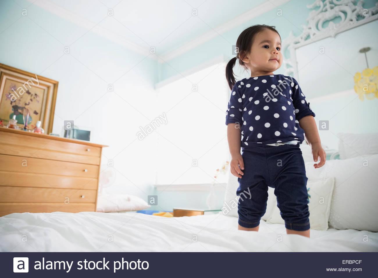 Brunette girl in polka-dot shirt standing on bed - Stock Image