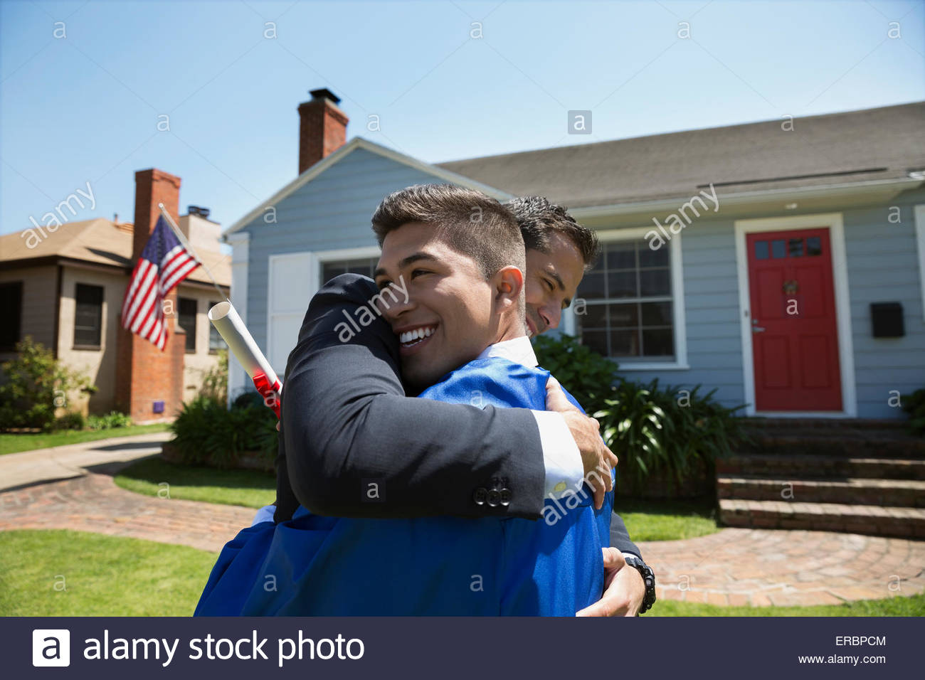 Father and graduate son hugging in front yard - Stock Image
