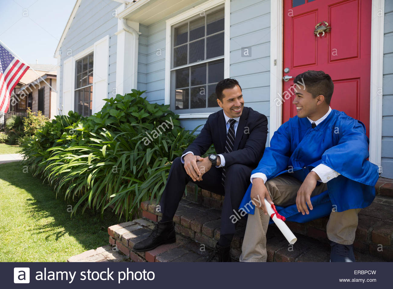 Father and graduate son with diploma front stoop - Stock Image