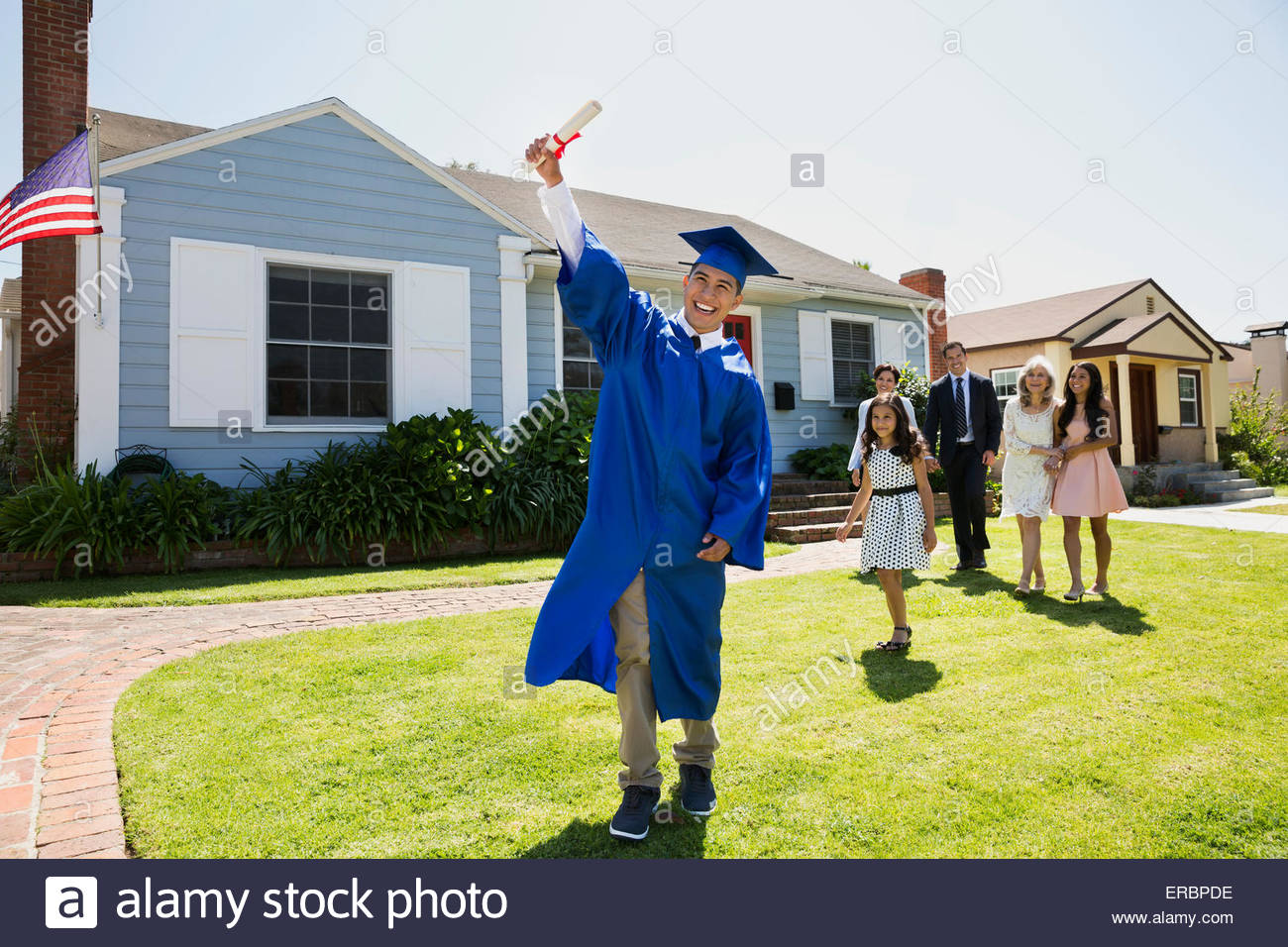 Exuberant graduate holding diploma with family front yard - Stock Image