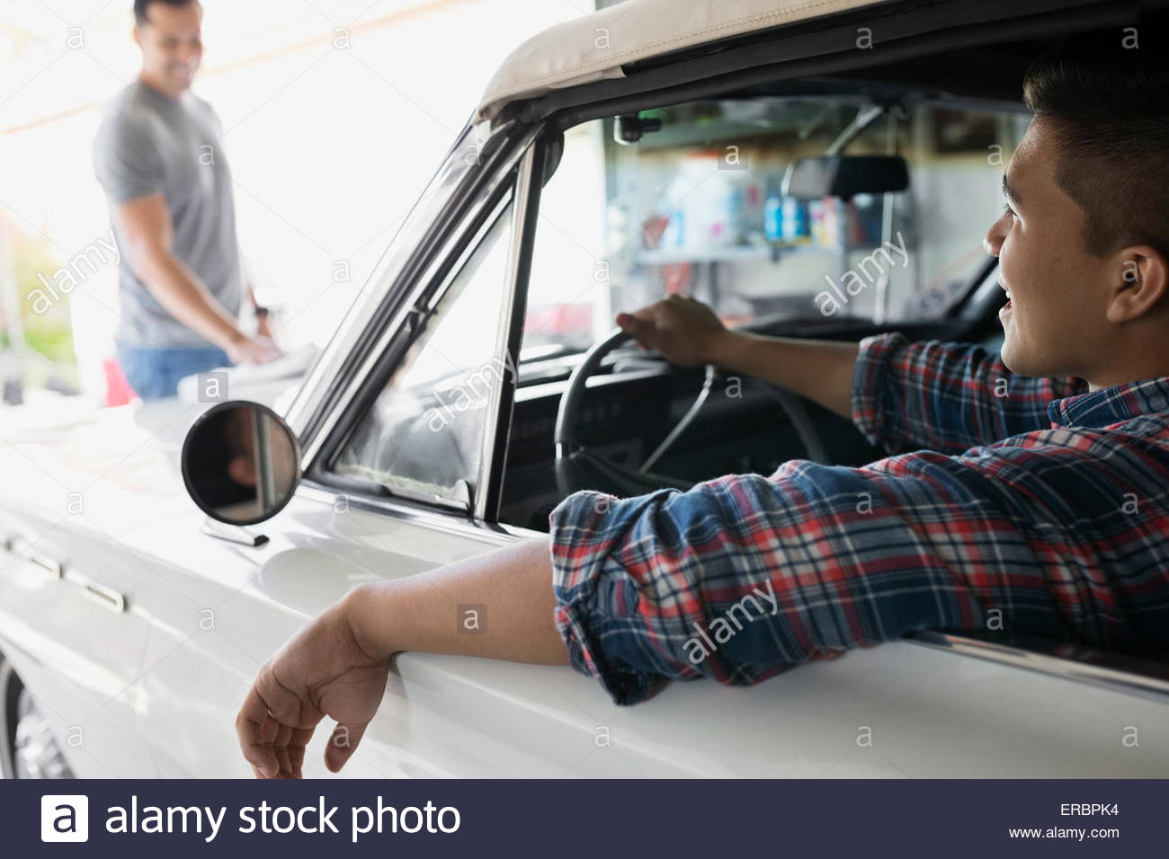Father and son with vintage car in garage - Stock Image