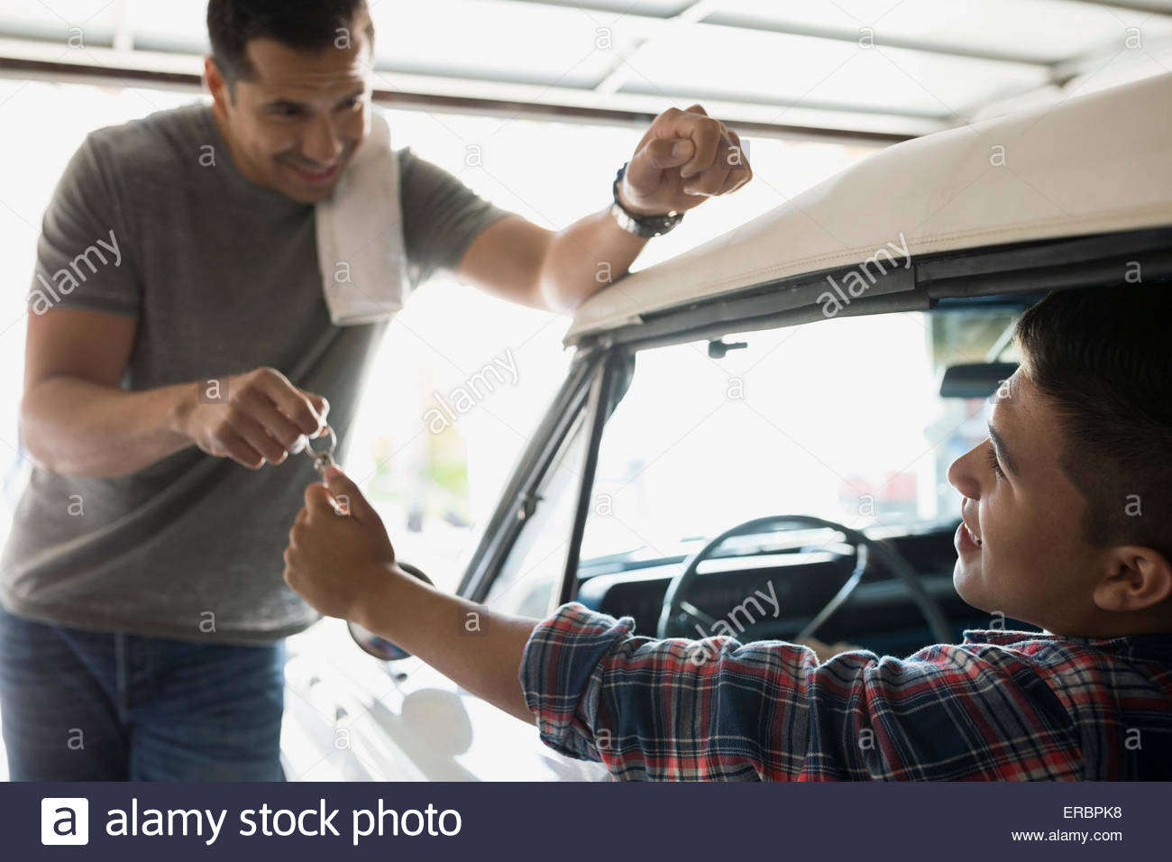 Bon Father Giving Son Keys To Vintage Car In Garage   Stock Image