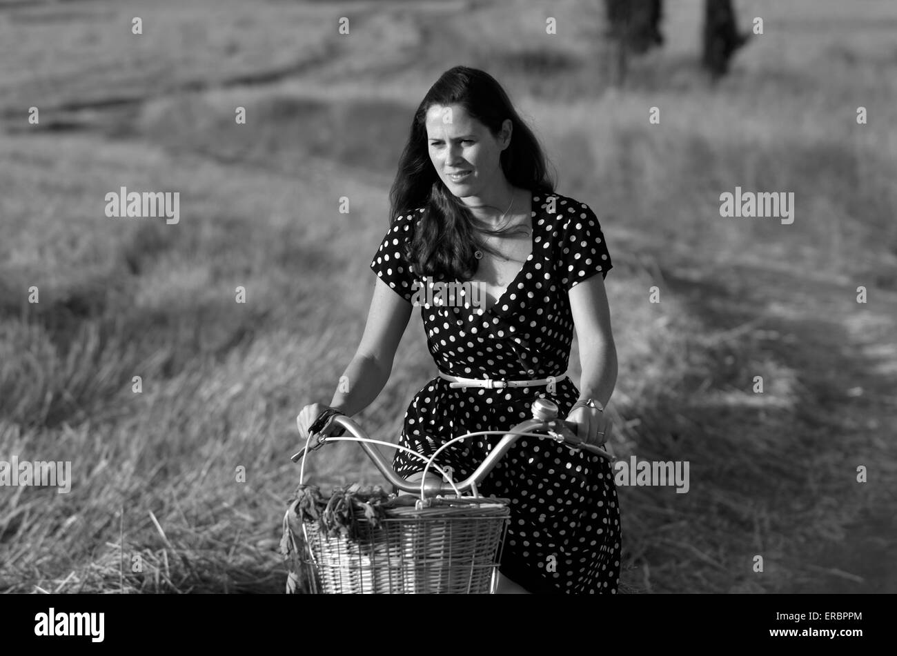 Young woman wearing a dress riding vintage bicycle in the field during sunset on hot summer day. Concept photo woman - Stock Image