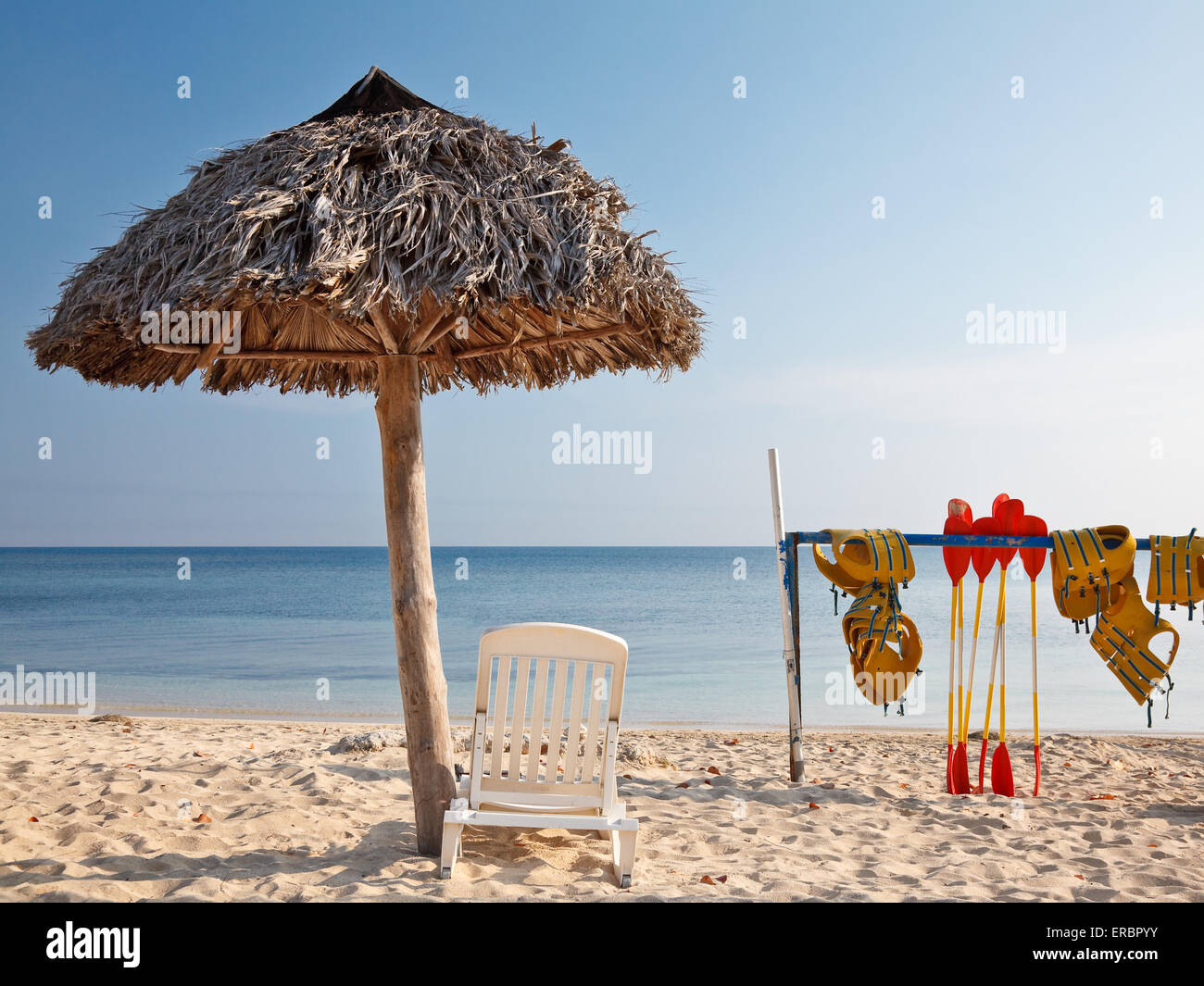 Caribbean tropical beach  with straw umbrella and watersport equipment - Stock Image
