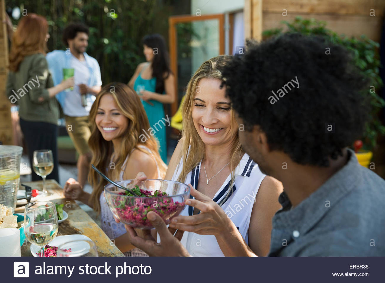 Friends eating and passing food at patio table - Stock Image