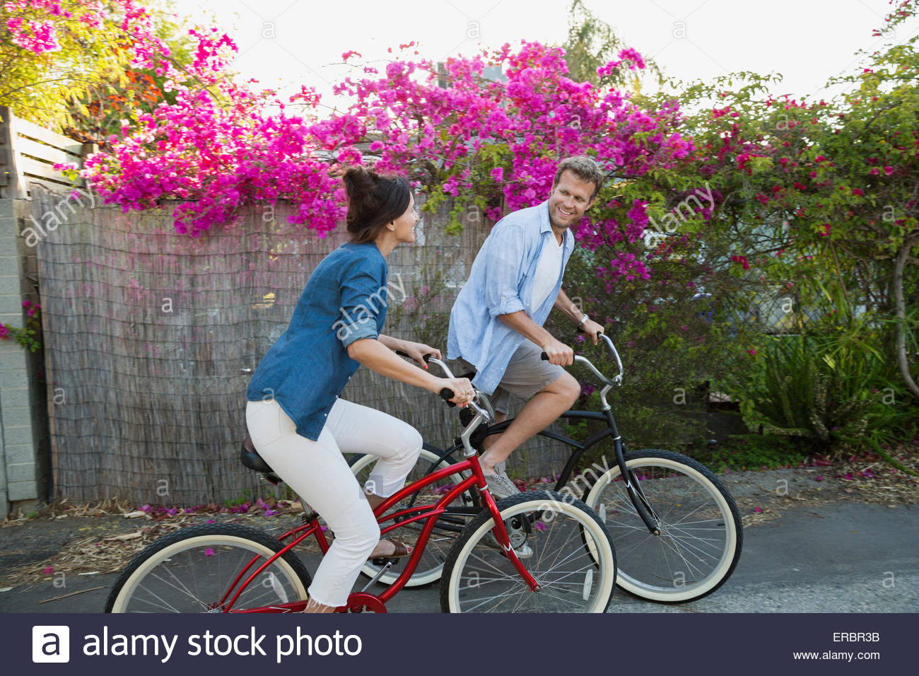 Couple riding bicycles along bougainvillea tree - Stock Image