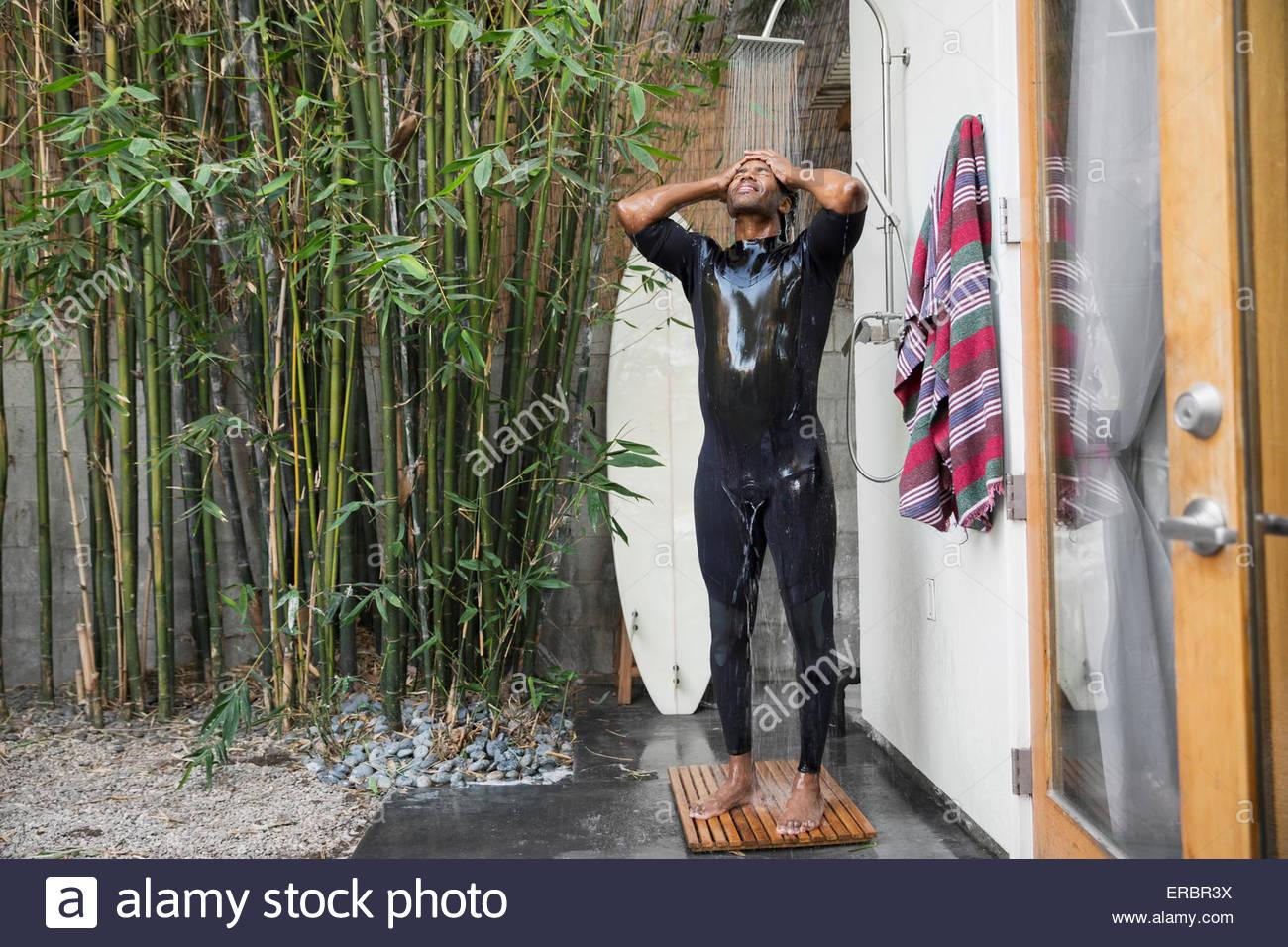 Man in wet suit surfboard using outdoor shower - Stock Image