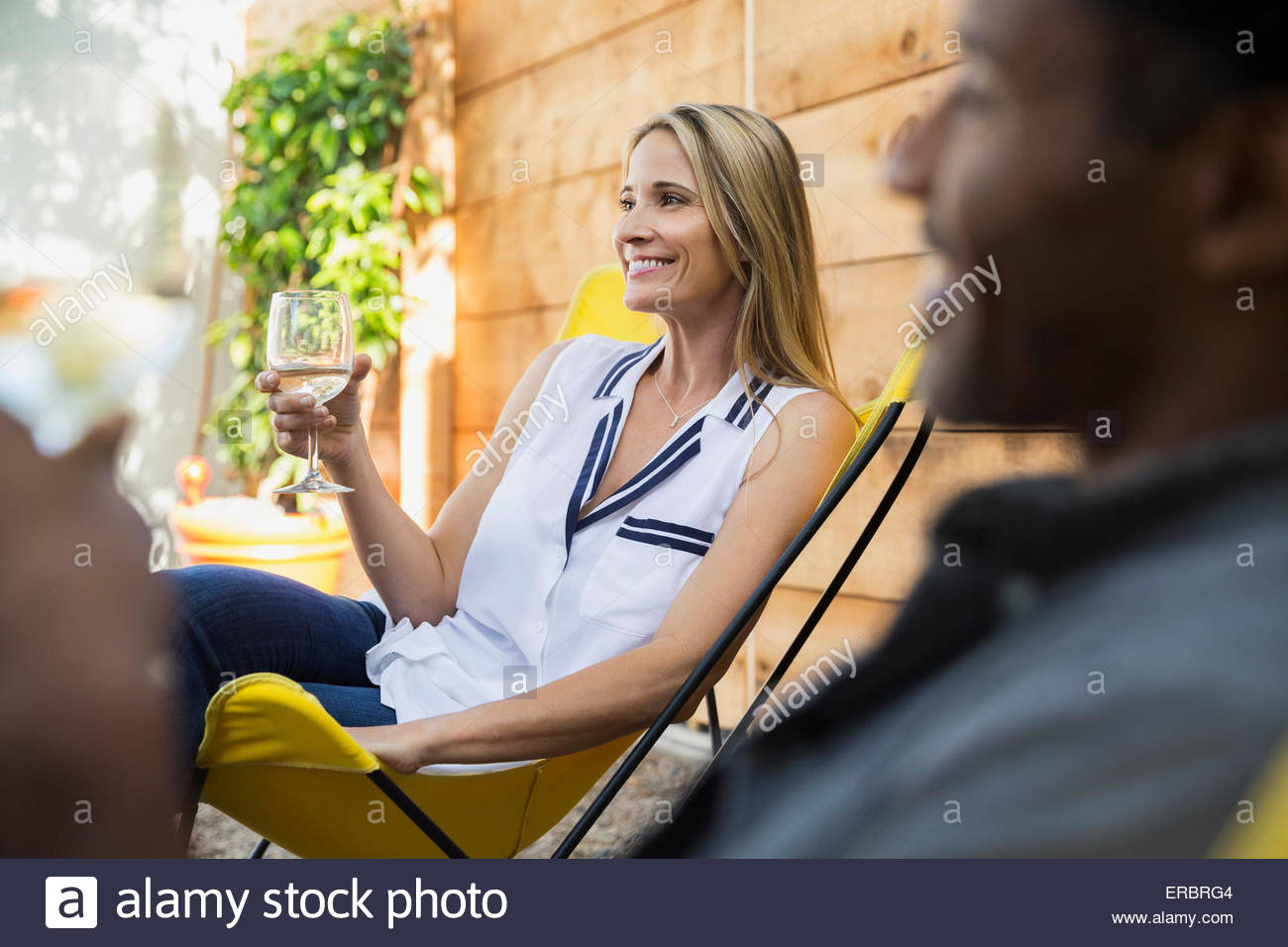 Smiling woman drinking wine on patio - Stock Image
