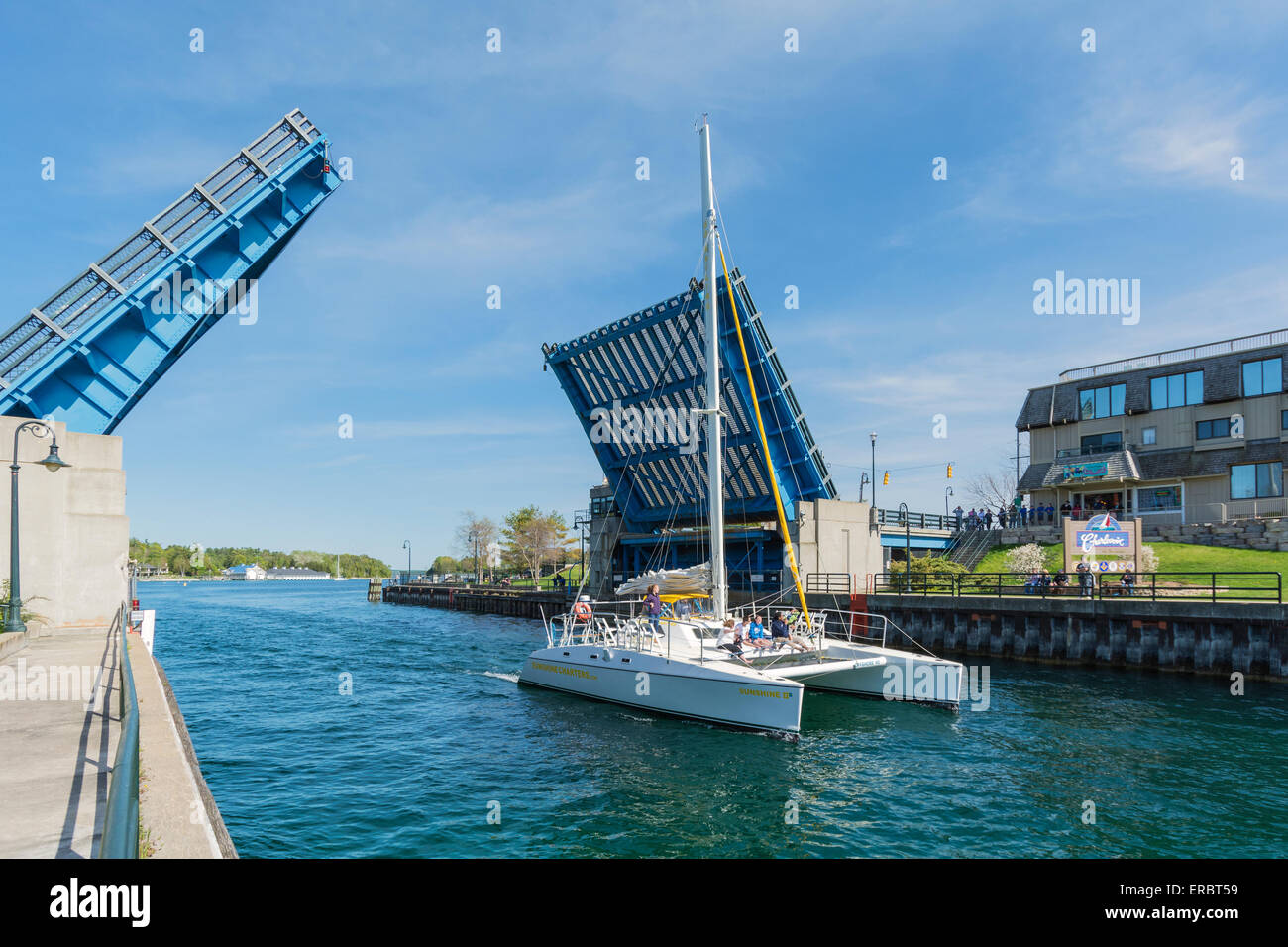 Michigan, Charlevoix, Pine River Channel, charter catamaran sailboat heads out to Lake Michigan, Bascule type drawbridge - Stock Image