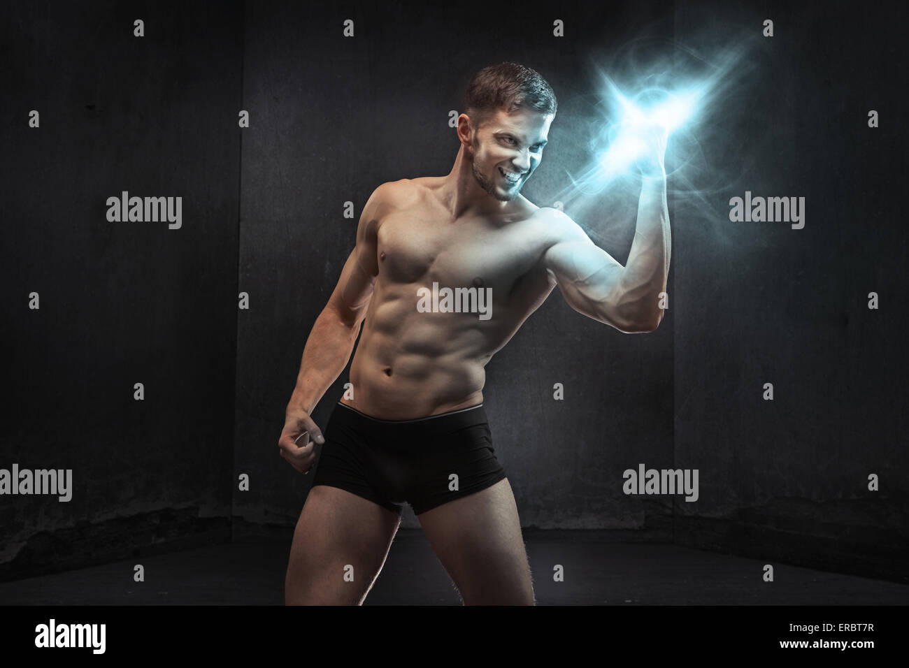 Muscular man squeezing the power - Stock Image