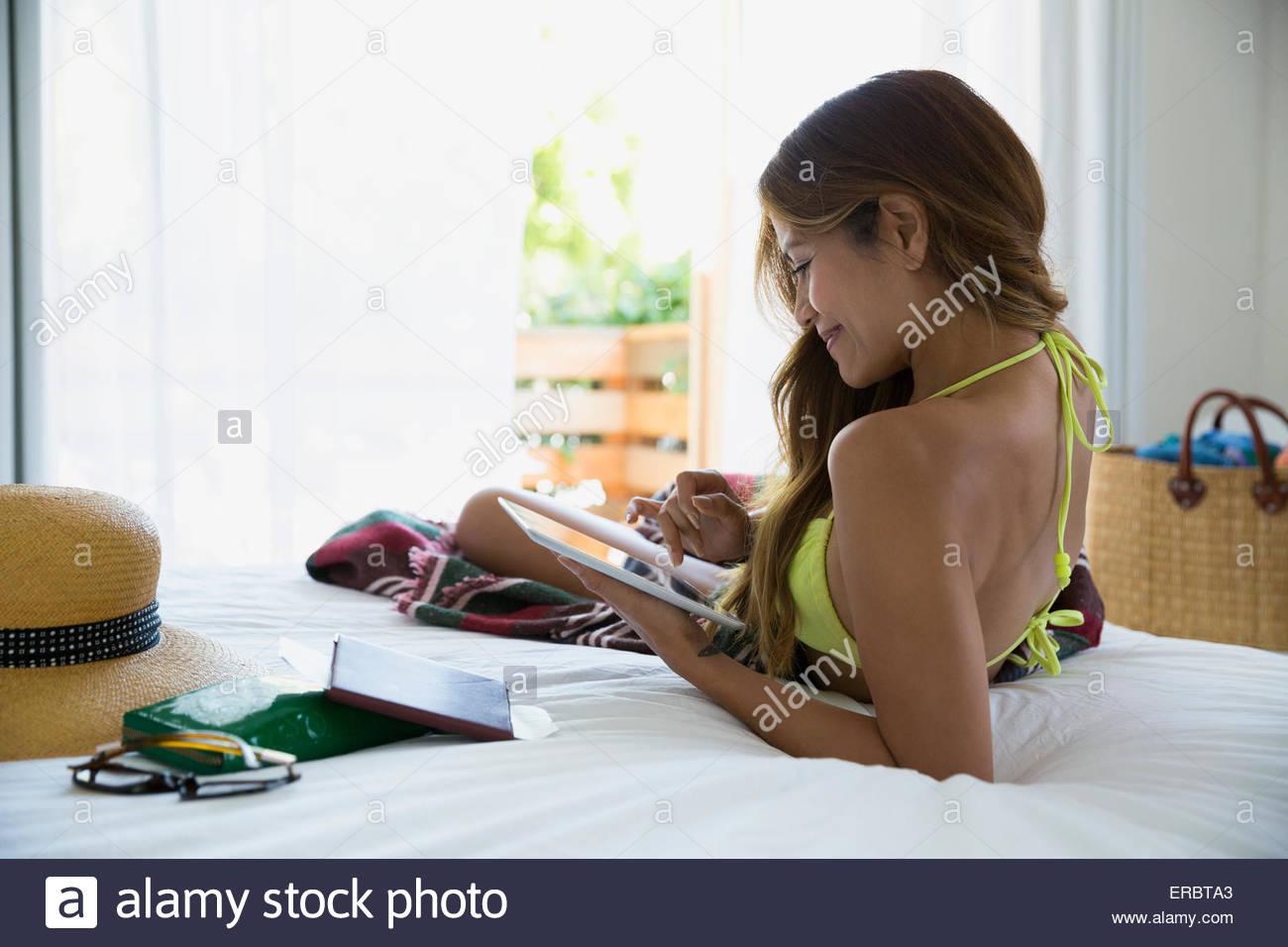 Woman in bikini using digital tablet on bed - Stock Image