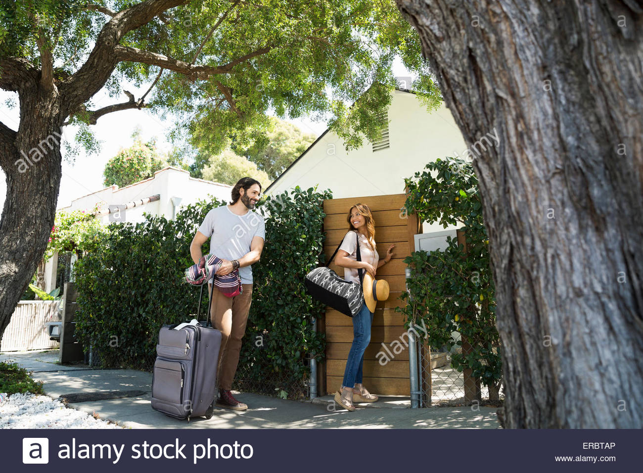 Couple with luggage arriving at vacation house gate - Stock Image