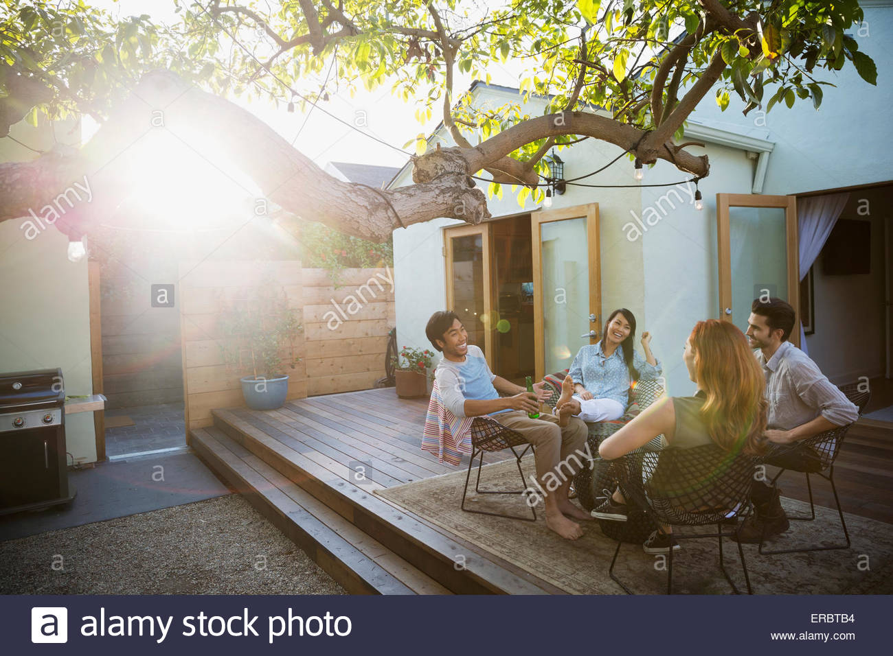 Friends drinking and talking on sunny patio - Stock Image