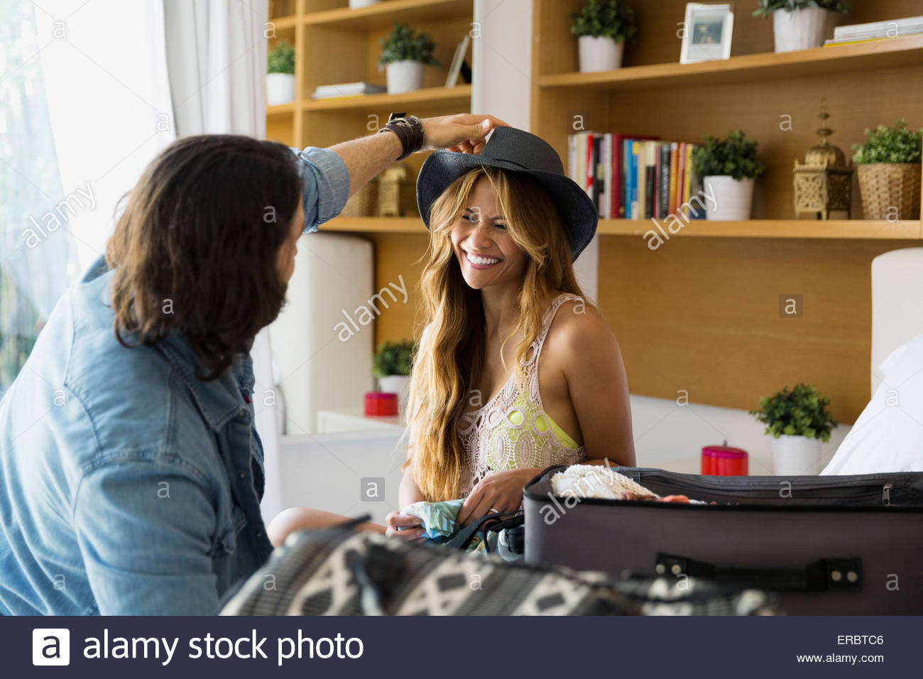 Man trying hat on woman near suitcase - Stock Image