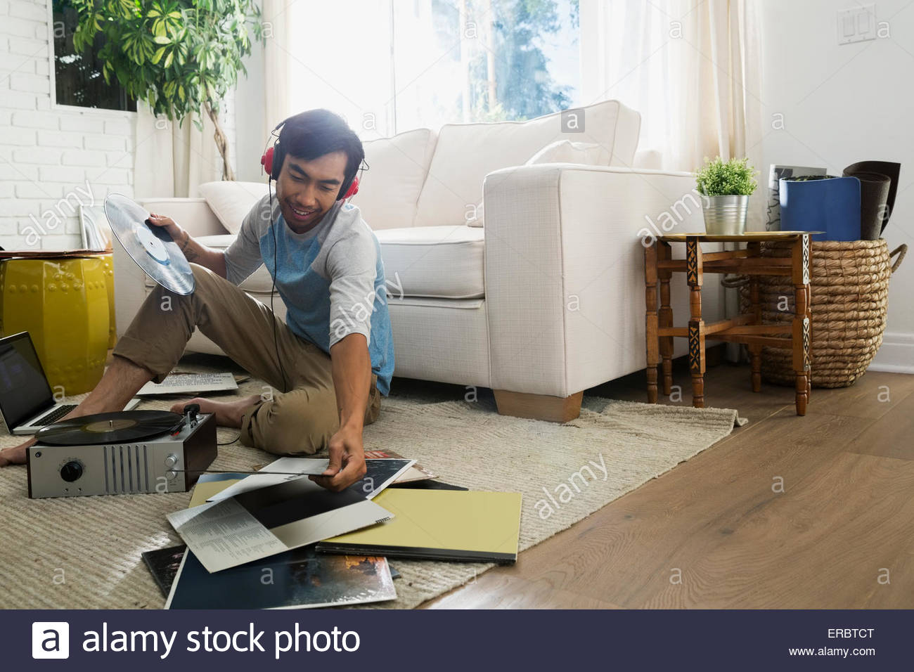 Man with headphones listening vinyl records living room - Stock Image
