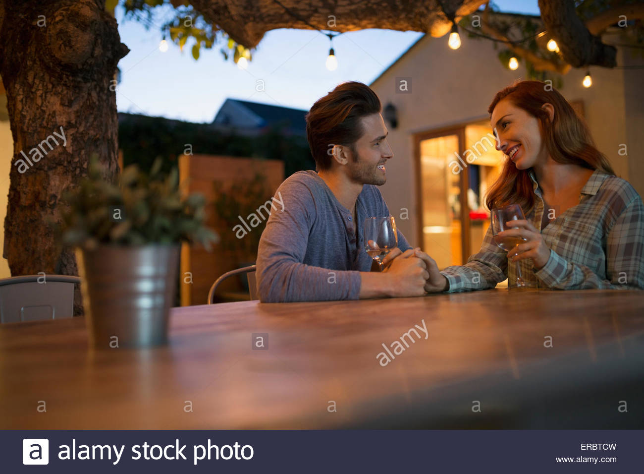 Affectionate couple drinking wine holding hands on patio - Stock Image