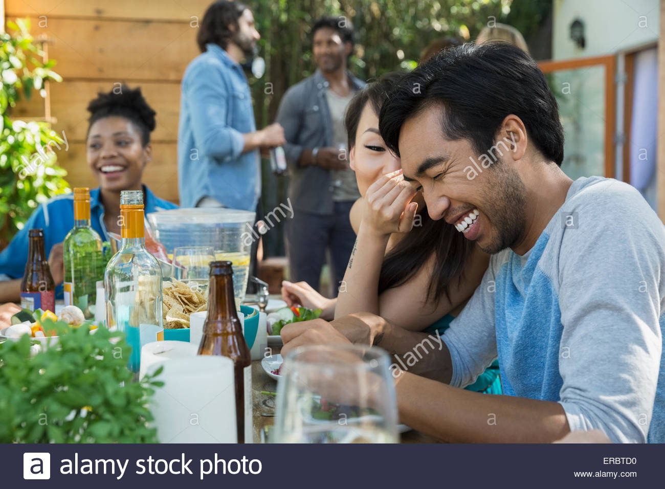 Woman whispering to laughing man at patio table - Stock Image