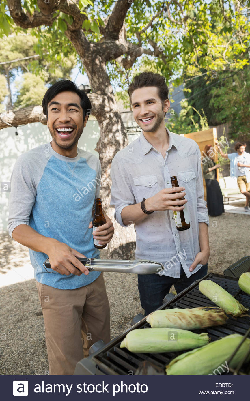 Smiling men drinking beer and barbecuing corn cobs - Stock Image