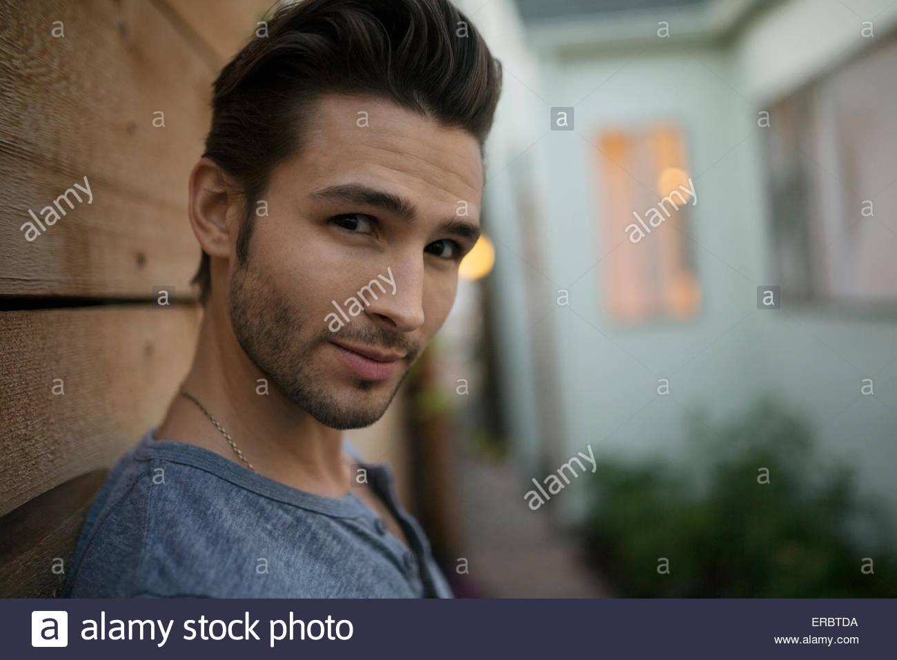 Portrait confident brunette man on patio - Stock Image